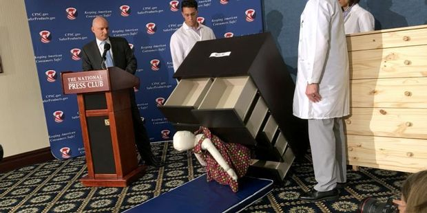 Consumer Product Safety Commission employees watch as a 13 kilo dummy falls over and under IKEA Malm model chest of drawers. Photo / AFP