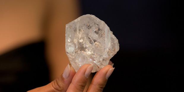 A model poses for photographs holding up the largest gem-quality rough cut diamond discovered in over 100 years. Photo / AP