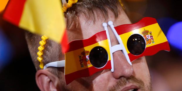 A follower of Spain's acting Primer Minister and candidate of Popular Party Mariano Rajoy, celebrates the election results in Madrid. Photo / AP