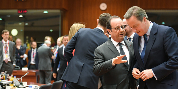 British Prime Minister David Cameron, right, speaks to French President Francois Hollande during a round table meeting at an EU summit in Brussels. Photo / AP