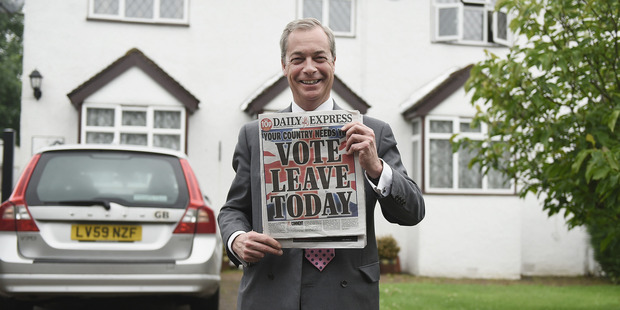 Nigel Farage holds up the 'Daily Express' as he returns to his home after buying newspapers of the United Kingdom before the EU referendum. Photo / Getty Images