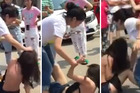 A woman cowers as she is attacked by a group who believe she is having an affair with one of their husbands. Photos / YouTube