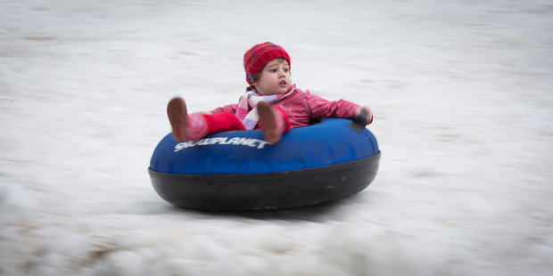 Loading Emma Martin, 3, enjoys a ride on the imported snow hill at Royal Reserve, Massey. Photo / Greg Bowker