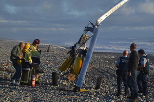 Pilot John Saunders, at left holding his helmet, inspects his crashed gyrocopter on the Greymouth beach.