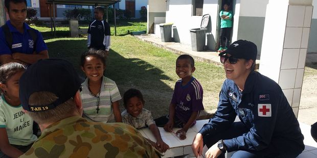 Corporal Alex Taylor, a senior medic from the Royal New Zealand Air Force, engages with primary school students in Gleno village in Timor-Leste. Photo / Supplied
