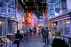 Tourists stroll along the Diagon Alley movie set at The Making of Harry Potter experience in London. Photo / AP