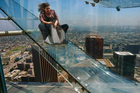 A frightened looking member of media is launched down Los Angeles' Skyslide. Photo / AP