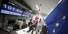 Money traders monitor computer screens with the day's exchange rate near flags of United Kingdom and EU. Photo / AP