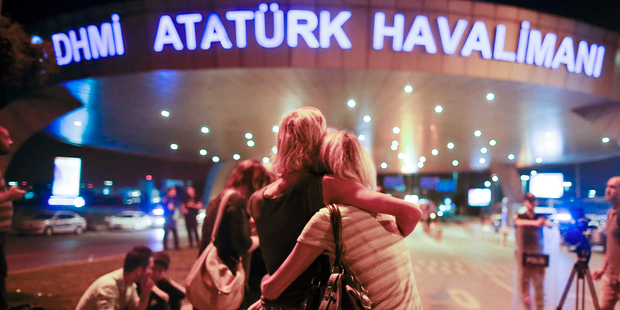 Passengers embrace each other at the entrance to Istanbul's Ataturk airport. Photo / AP