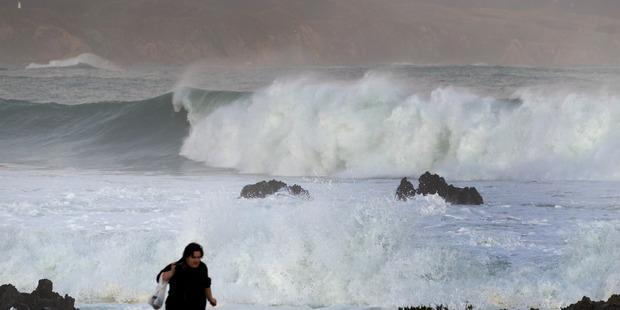 Sightseers watching huge ocean swells between Owhiro Bay and Island Bay, Wellington. Photo / Mark Mitchell
