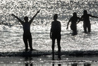 A group of friends take to the ocean for an early morning swim at Mt Maunganui. Photo / Alan Gibson