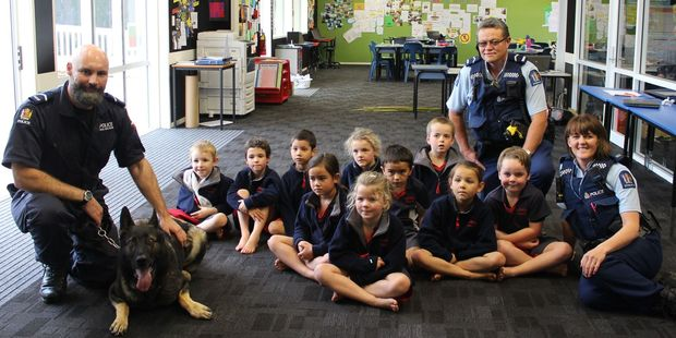 Police dog handler Simon Mercer (left) with  5-year-old Carne and junior students at Weber School, with Senior Constable Dave Kirk and Constable Maxine Walshe. Photo / Christine McKay