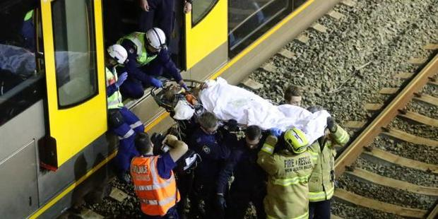 Rescuers work to free the man, who fell under an oncoming train. Photo /  Bill Hearne