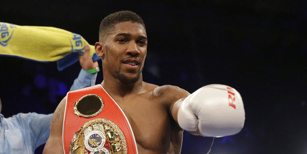 British boxer Anthony Joshua holds his belt fanned by his father Robert after defeating U.S. boxer Dominic Breazeale. Photo / AP