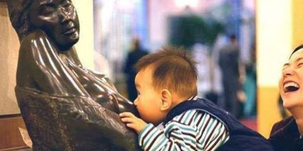 The hungry young boy escapes his mother's grasp and latches onto the breast of a statue hoping to be fed. Photo / Facebook