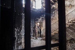 A Swat soldier looks at the building where they found an Isis prison in Fallujah. The downstairs rooms were used as group cells, and the upstairs for solitary confinement. Photo / The Washington Post
