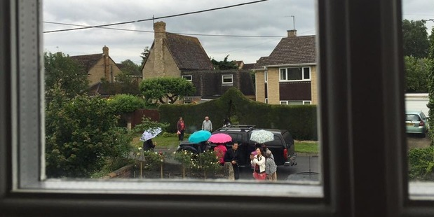 The tourists braved the rain and carried umbrellas. Photo / Janis Harwood, Facebook