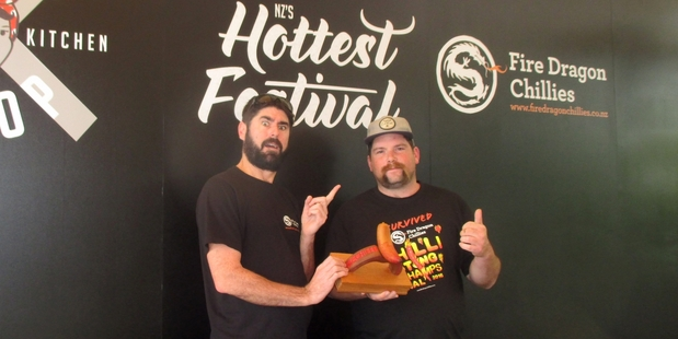 FIRE IN THE HOLD: Clint Meyer, from the Hokianga-based natural chilli sauce manufacturer Fire Dragon Chillies, presents the championship title to Josh Shotter for winning the New Zealand Chilli Eating Championship in Auckland.PHOTOS/SUPPLIED