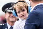 Prince George, wears earmuffs against the roar of aircraft as he visits with his father Prince William. Photo / AP