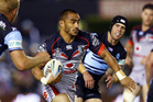 Thomas Leuluai makes a break against the Sharks. Photo / Getty Images