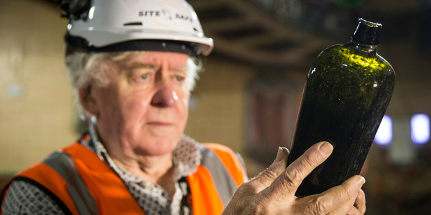 George Farrant studies an old bottle discovered in the ground underneath the St James Theatre. Photo / Jason Oxenham
