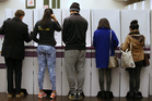 Voters fill in their ballots at a polling station at Town Hall in Sydney. Photo / AP