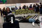 Passengers walk past a banner that reads