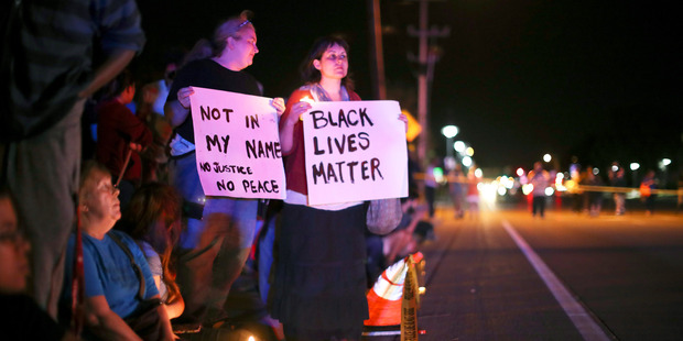 Demonstrators hold signs across the street from the scene of the shooting. Photo / AP