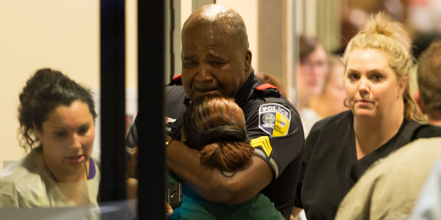 Loading A Dallas Area Rapid Transit police officer receives comfort at the Baylor University Hospital emergency room entrance. Photo / AP