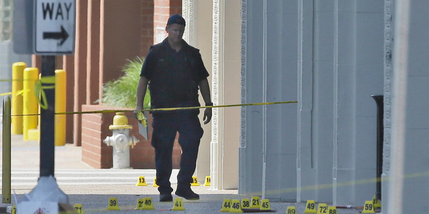 Loading An investigator walks the scene of a shooting in downtown Dallas. Photo / AP