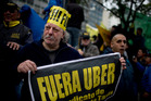 A Buenos Aires taxi driver holds a sign that reads