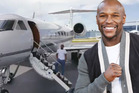 Floyd Mayweather stands on the steps of one of his private jets.