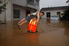 A rescue worker lifts a child through flood waters as residents are evacuated. Photo / AP