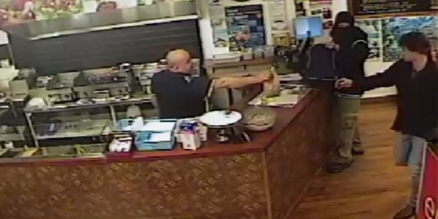 Loading Unfazed, the man continues finishing the order, reaching right past the offender to hand it to a customer in the Christchurch fish shop. Photo / Canterbury Police Shop