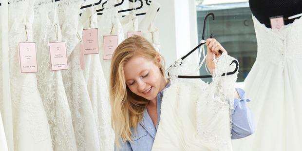 Bride Choosing Dress In Bridal Boutique