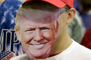 AJ Garrett holds a mask of Republican presidential candidate Donald Trump before a rally in Westfield, Indiana. Photo / AP