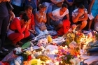 People pay homage to the victims of a truck attack at a makeshift memorial near the area where a truck mowed through revelers in Nice, southern France. Photo/AP