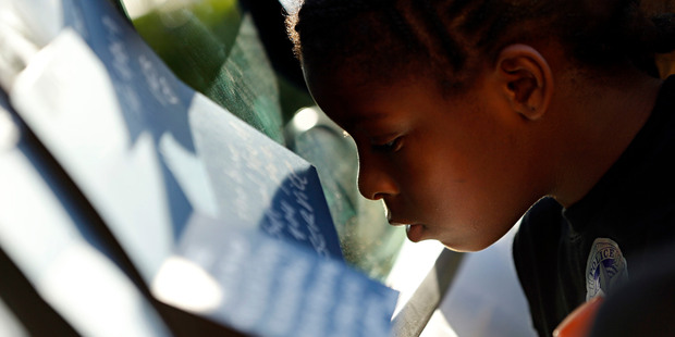 London Lockhart looks over cards left on a Dallas police cruiser, outside police headquarters in Dallas. Photo / AP