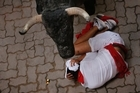 A reveler covers his head after falling besides a fighting bull during the running of the bulls. Photo/AP