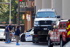 FBI agents check the scene around a police vehicle as it is lifted onto a hauler in the crime scene area in Dallas. Photo / AP