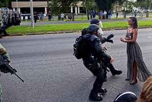 A protester is grabbed by police officers in riot gear after she refused to leave the motor way in front of the the Baton Rouge Police Department Headquarters. Photo / AP