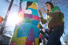 Auckland crochet designer Alia Bland yarn bombs a tree in Greerton. Photo / Alan Gibson