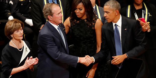 US President Barack Obama and former president George W Bush shake hands as first lady Michelle Obama, and Laura Bush (left) stand by at the Dallas memorial service. Photo / AP