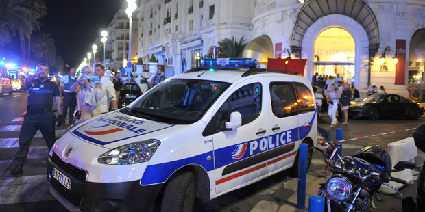 Police talk to witnesses outside the hotel Negresco, which was used to treat the injured. Picture / AP