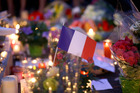 A French flag sits between flowers and candles at a makeshift memorial to commemorate the victims of the Nice attack. Photo / AP