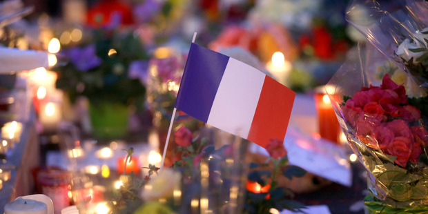 Loading A French flag sits between flowers and candles at a makeshift memorial to commemorate the victims of an attack near the area where a truck mowed through revelers in Nice. Photo / AP