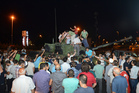 People stand and gather around a tank after they stopped it in Istanbul. Photo / AP