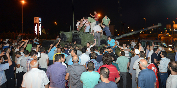 Loading People stand and gather around a tank after they stopped it in Istanbul. Photo / AP