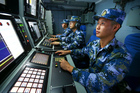 Chinese navy sailors on board the missile destroyer Hefei search for targets during a military exercise in the South China Sea. Photo / Xinhua via AP