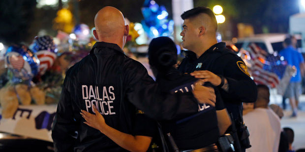 Dallas police officers comfort each other in front of police cars decorated as a public memorial Friday. Photo / AP